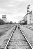 Young girls walking down railroad track. Two teenage girls walking down railway track black white Stock Images