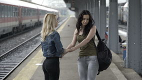 Young girls walking hand in hand in train station hugging  before separation stock footage