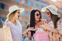 Young girls walking the street with shopping bags. Happy shopping with smiles royalty free stock photo