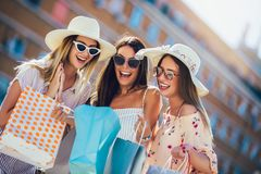 Young girls walking the street with shopping bags. Happy shopping with smiles stock images