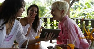 Young girls watch photos on digital tablet sitting at table on terrace in summer tropical forest together laughing. Group of beautiful women communicating slow stock video footage