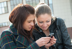 Young girls watch something in mobile phone. Two happy girls watch something in mobile phone Royalty Free Stock Photography