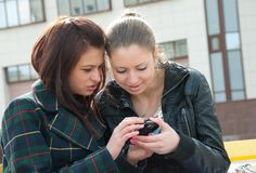 Young girls watch something in mobile phone Stock Photo