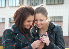 Young girls watch something in mobile phone royalty free stock photo