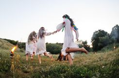 The celebration of the pagan Slavic holiday of Ivan Kupala Day or Midsummer. Young girls in white shirts and wreaths of flowers on the background of a fire. The Royalty Free Stock Photo