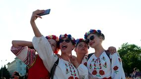 Young girls in wreaths and embroidery, national costumes make selfie on mobile phone in backlit stock video