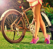 Young  girlwith bike in the park Stock Photography