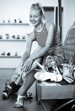 Young glad girl trying on chosen shoes Stock Photography