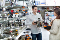 Young glad positive  couple in the cookware section Royalty Free Stock Images