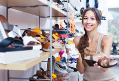 Young glad woman choosing pair of summer shoes Royalty Free Stock Images
