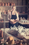 Young glad woman potter carrying ceramic vessels stock image