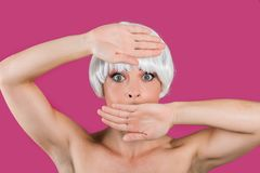 Young glam model covering mouth. Charming model in short white wig framing face with hands looking shocked at camera Stock Photography