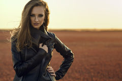 Young glam model with the wind in her long hair wearing black stylish leather jacket standing in the deserted field at sunset. Young beautiful glam model with Royalty Free Stock Photo