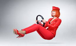 Young glamor girl in red driver car with a wheel Royalty Free Stock Photos