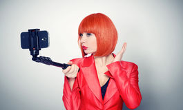 Young glamor girl in red making selfie with a stick Royalty Free Stock Photo