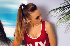 Young glamour girl in red body swimsuit. At the beach Royalty Free Stock Photo