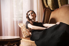 Young glamour woman on beige sofa Stock Photo