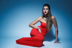 Young glamour woman in red dress long hair Royalty Free Stock Image