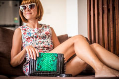 Young glamour woman wearing flower dress posing with luxury handmade snakeskin python handbag. Beautiful stylish girl Stock Images