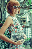 Young glamour woman wearing flower dress posing with luxury handmade snakeskin python handbag. Beautiful stylish girl Royalty Free Stock Photo