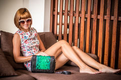 Young glamour woman wearing flower dress posing with luxury handmade snakeskin python handbag. Beautiful stylish girl Stock Photography