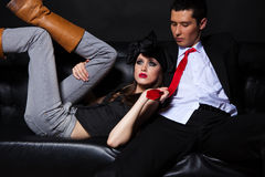 Young glamourous loving couple on black sofa. Royalty Free Stock Photos