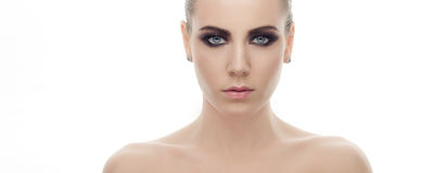 Young gloomy fashionable woman with bare shoulders and gorgeous dark smokey makeup posing on white studio background Royalty Free Stock Images