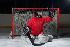 Young goalkeeper catching a puck Royalty Free Stock Image