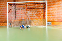 Young goalkeeper missed the soccer ball. Allowing through a goal on an indoor soccer court as he lies on the ground between the posts Stock Image
