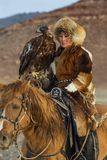 Young Golden Eagle Huntress during hunting with birds of prey to the hare in desert mountain of Western Mongolia. SAGSAY, MONGOLIA - SEP 28, 2017: Young Golden Stock Photos