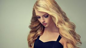 Golden haired woman with voluminous, shiny and curly hairstyle.Frizzy hair. Young golden haired woman with voluminous, shiny and wavy hair . Beautiful model royalty free stock image