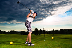 Young golf player on course doing golf swing Royalty Free Stock Images