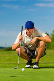 Young golf player on course putting. He aiming for his put shot Royalty Free Stock Image