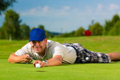 Young golf player on course putting. He aiming for his put shot Royalty Free Stock Photos