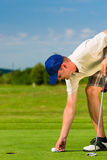Young golf player on course putting Stock Images