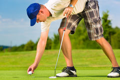 Young golf player on course putting Royalty Free Stock Image
