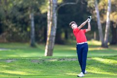 Young golf player hits a driver shot from the tee on a golf cour stock images