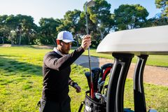 Young golf player keeps a stick in his bag next to a golf cart royalty free stock image