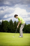 Young golf player putting. Royalty Free Stock Images
