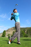 Young golfer. Hitting a shot with an iron Stock Photo