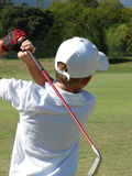 Young Golfer. Young boy following his ball after an iron shot on the golf course Royalty Free Stock Image