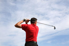 Young Golfer. Hitting an iron against a half cloudy sky Royalty Free Stock Photography