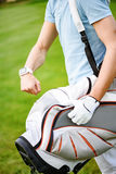 Young golfer checking time on smartwatch. Exactly on time. Close up of young golfer checking time on beautiful golf course, holding his bag while walking to next Royalty Free Stock Photo