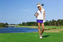 Young golfer girl on golf course Royalty Free Stock Image