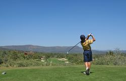 Young golfer hitting a golf shot. Young golfer hitting a golf ball tee shot in the mountains Stock Image