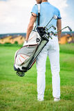 Young golfer holding golf bag royalty free stock images