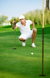 Young golfer lining up a putt. Young golfer lines up his eagle putt Royalty Free Stock Image