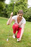 Young golfer. A young golfer placing the ball on the tee Royalty Free Stock Images
