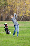 Young golfer swing. Young golfer playing a shot from the fairway. Blonde caucasian kid. Autumn Season Stock Photos