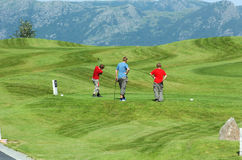 Young Golfers. Three young golfers on a beautiful large golf resort with mountains in background Stock Photography